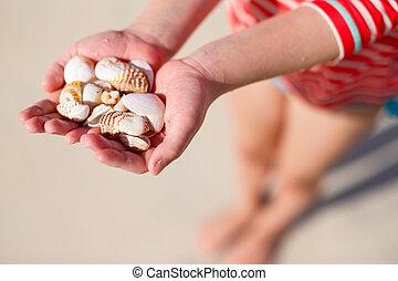 Girl holding sea shells