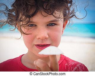 Girl holding shell on beach