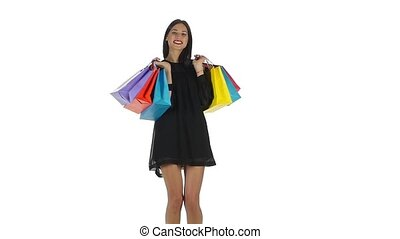 Joyful teenager holding shopping bags and laughing and smiling, woman holding shopping bags, shopping woman holding shopping bags above her haed smilling happy during sale shopping spree, beautiful young female shopper, people and fashion, on white background, slow motion