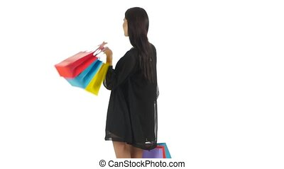 Girl holding shopping bags and laughing and smiling. White