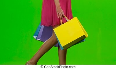 Girl holding shopping bags, woman with shopping bags walking in the mall, woman with shopping bags walking, woman holding shopping bags, woman holding shopping bags, woman holding shopping bags, beautiful young female shopper, people and fashion, on green screen, slow motion