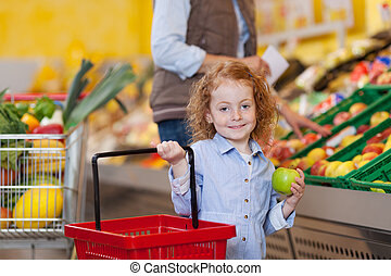 Girl Holding Shopping Basket And Apple At Grocery Store