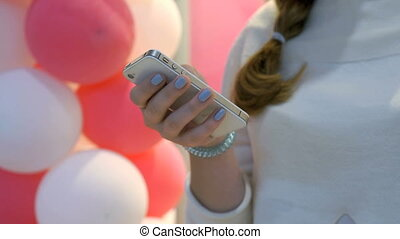 Girl holding smartphone on background of balloons