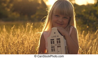 Girl holding toy house