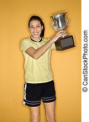 Girl holding trophy.