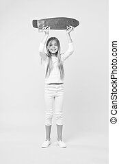 Girl holding violet skateboard above her head. Champion in street race, happy childhood concept. Kid in white jumper, jeans and sneakers isolated on pink background. Child with pretty smiling face