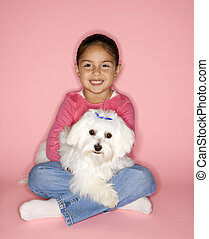 Girl holding white Maltese dog.