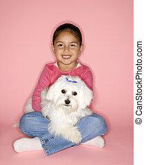 Girl holding white Maltese dog.