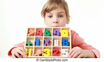 girl holds a box with cells and looks at wooden figures in it