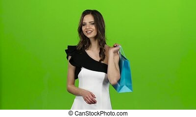 Girl holds a gift bag in her hands, she likes it. Green screen. Slow motion
