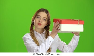 Girl holds a gift in her hands and is glad. Green screen