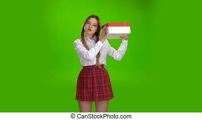 Girl holds a gift in her hands and is pleased. Green screen