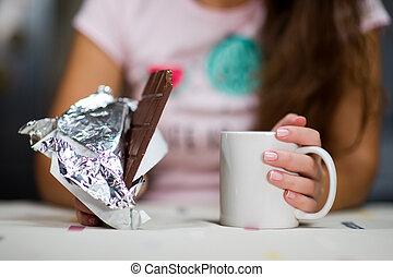 girl holds a mug of tea and chocolate bar on a table, close-up