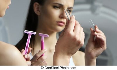 Girl holds a pair of tweezers and a razor, and chooses what...