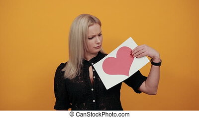 Beautiful blonde girl in black dress on yellow background holds a piece of paper with red heart and touches her tongue with finger