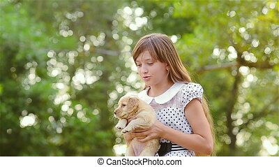 Girl holds a puppy on hands