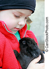 Girl holding a little baby rabbit , looking at him .