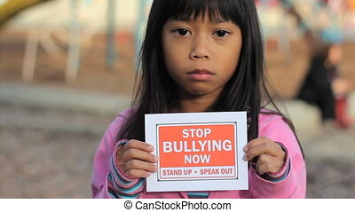 Girl Holds A Stop Bullying Sign - A sad Asian girl holds up...