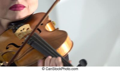 Girl holds a violin playing her bowing over the strings. Close up. White background