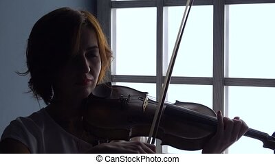Girl holds a violin plays on it by fingering the chords with a bow against the window. Silhouette