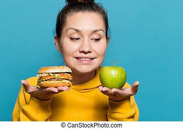 girl holds an apple and a burger on the palms near her face and smiles, looking at the apple
