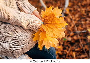 girl holds autumn leaves on the background of forest