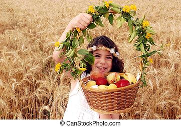 Girl Holds Basket of Fruit in Field of Wheat - A little girl...