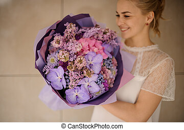 Girl holds bouquet of various purple flowers