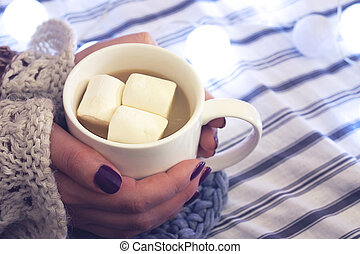 Girl holds coffee with marshmallow.
