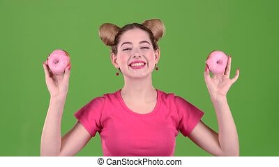 Girl holds donuts in her hands and closes her eyes. Green screen