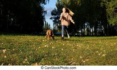 Happy girl holds furry spaniel on red leash and runs along green park lawn slow motion