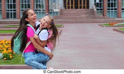 girl holds happy friend having fun near school building - ...
