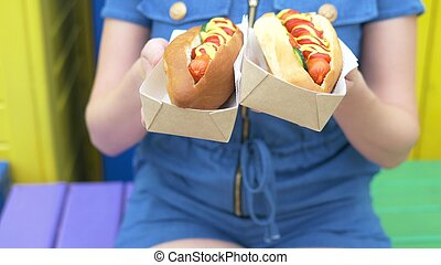girl holds in her hand two delicious hot dogs on the street on a summer day