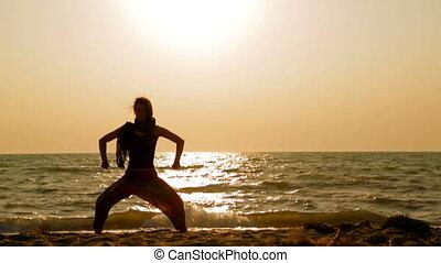 girl holds meditation on the beach