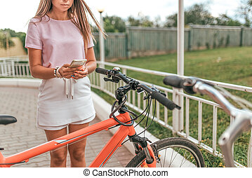 Girl holds mobile phone hand, photographs parking bicycle. In summer city application online, Internet post in social networks. Concept losing bike, finding route on city map, a tourist trip.