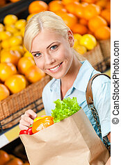 Girl holds paper bag with fresh vegetables