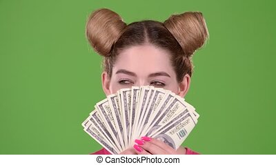 Girl holds paper bills and winks. Green screen. Close up -...