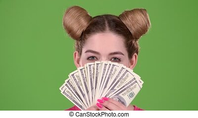 Girl holds paper bills and winks. Green screen. Close up....