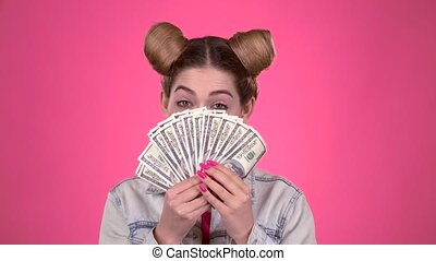 Girl holds paper bills and winks. Pink background - Girl...