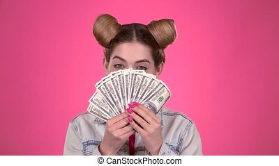 Girl holds paper bills and winks. Pink background. Slow motion