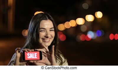 Girl holds phone with sale ad on screen at night -...