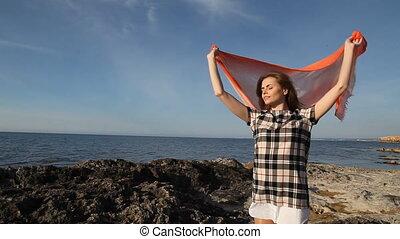 girl holds silk wind Beach rocks - girl holds silk develops...