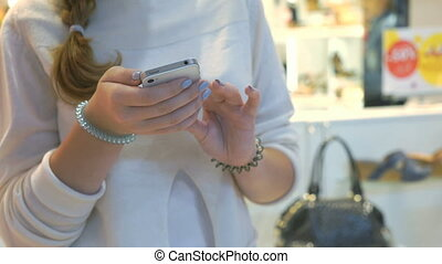 Girl holds silver smartphone. Close-up - Girl holding silver...