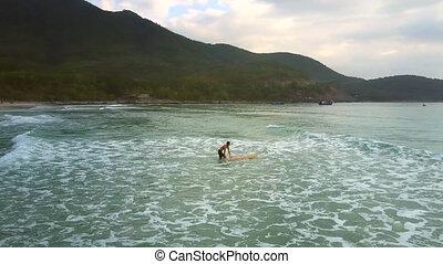 girl holds surfboard on water overcoming foamy waves - girl...