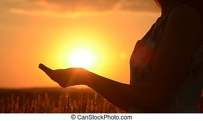 Girl holds the sun in hand