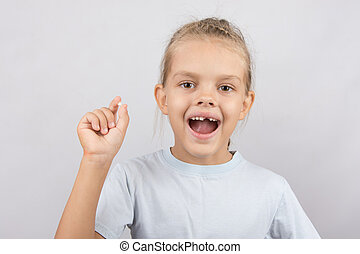 Girl holds the tooth in his hand and his mouth open showing a hole between the teeth