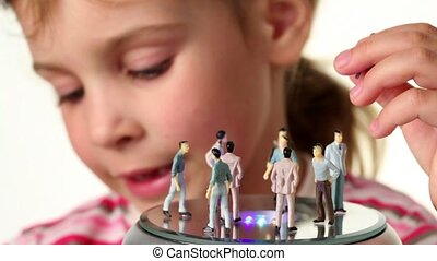 Girl holds toy figurines of woman, she decided to take one toy man from toy podium