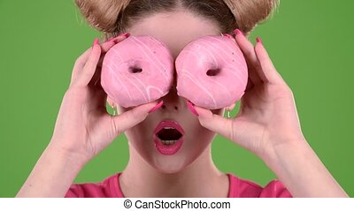 Girl holds two donuts in her hands and closes her eyes. Green screen. Close up