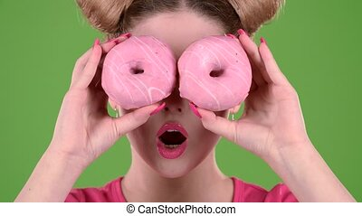 Girl holds two donuts in her hands and closes her eyes. Green screen. Close up. Slow motion