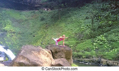 girl holds yoga pose on high rock by green slope